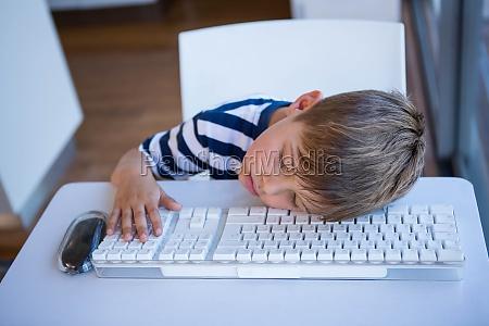 little boy slipping on keyboard