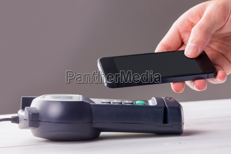 man, using, smartphone, to, express, pay - 15554735