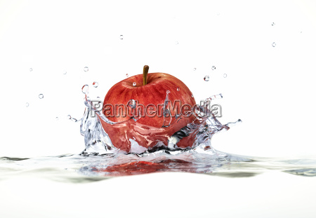 red apple splashing into water close