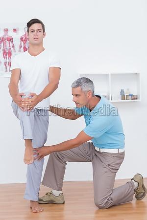 doctor examining his patient legs