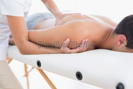 physiotherapist doing shoulder massage to her