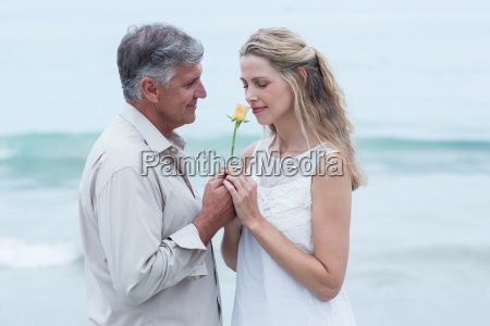 happy man offering flower to his