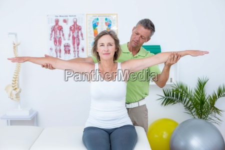 doctor stretching his patients arms