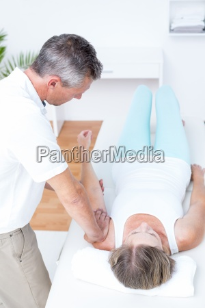physiotherapist doing arm massage to his