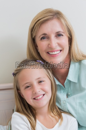 happy mother and daughter smiling at