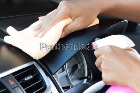 closeup hand cleansing car dashboard
