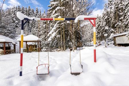 children playground under snow in the
