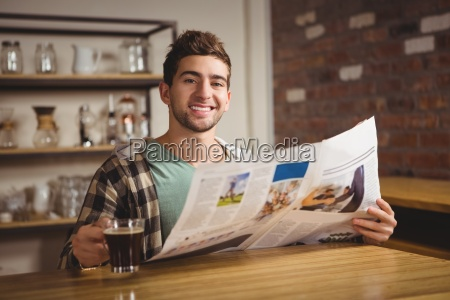 smiling hipster drinking coffee and reading