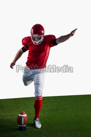 american football player kicking football