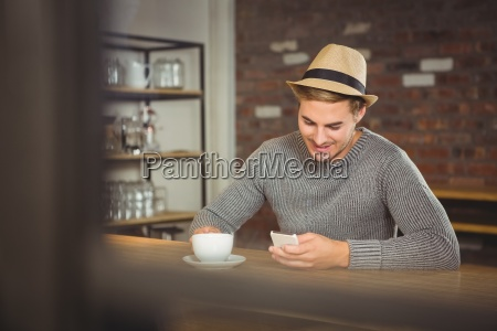 handsome hipster having coffee and using