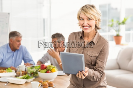 smiling casual businesswoman using tablet at