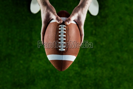 american football player holding up football
