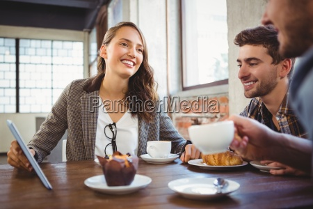 smiling friends enjoying coffee and using