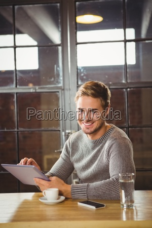 handsome man smiling and using tablet