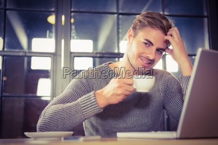 handsome man smiling and drinking coffee
