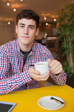 young man holding coffee cup at