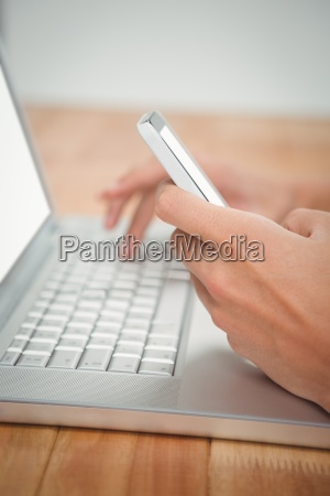 man using mobile phone while typing