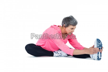 mature woman touching toes while exercising