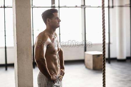 muscular shirtless man posing in crossfit