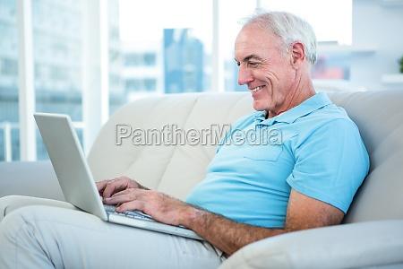 happy senior man sitting on sofa