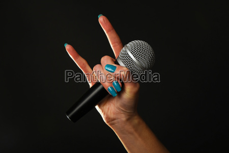 woman hand with microphone and devil