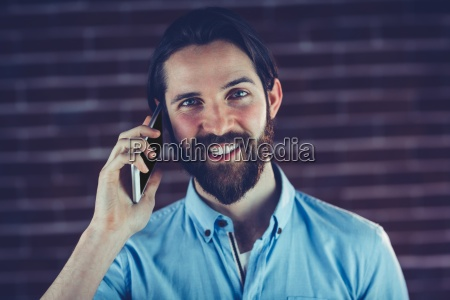 portrait of smiling hipster using smartphone