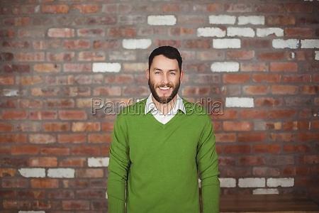 portrait of happy businessman standing against