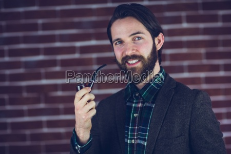 portrait of smiling handsome man smoking