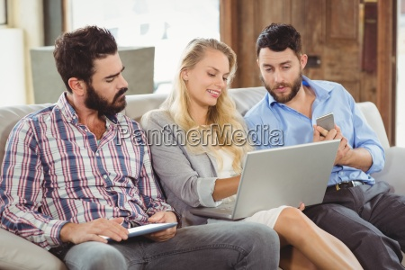 woman showing laptop to colleagues
