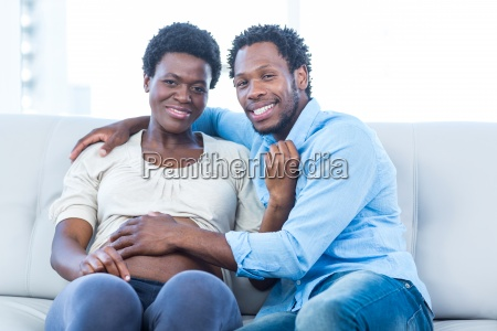 happy pregnant woman with husband sitting