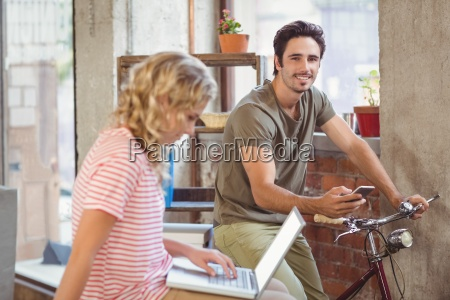 man on bicycle using smartphone in
