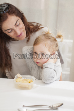 baby eating from tupperware with mother