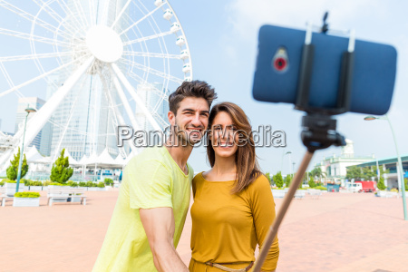 caucasian couple use the selfie stick