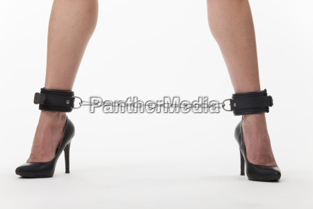 female feet in chains on white