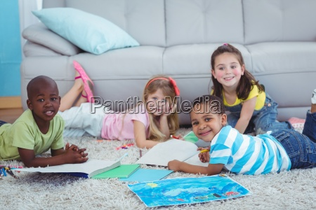smiling kids drawing pictures on paper