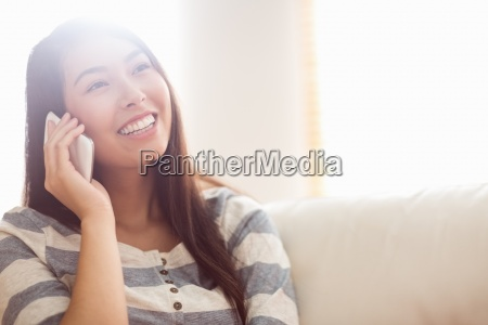 smiling asian woman on couch using