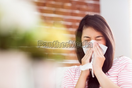 asian woman blowing her nose on