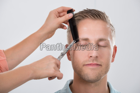 young man getting his eyebrow trimmed