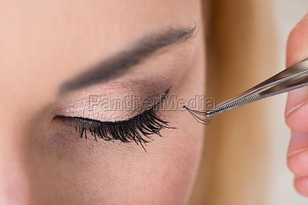 hand putting false eyelashes on woman