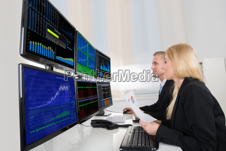 business people analyzing data displayed on