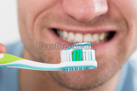 closeup of man brushing teeth