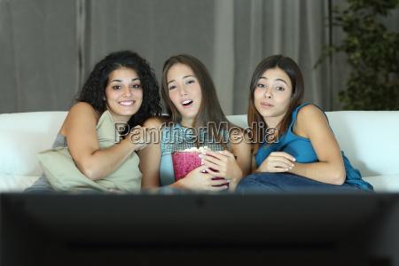 three friends watching romantic movie on