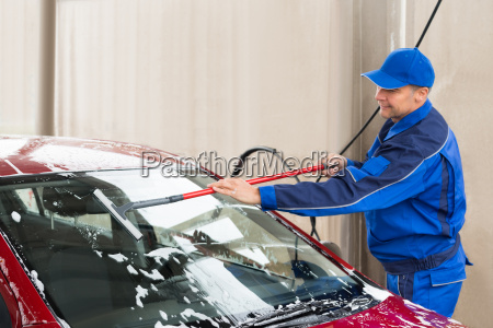 worker washing windshield of car at