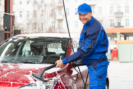manual worker washing car at service