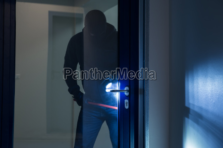 burglar using crowbar to open glass
