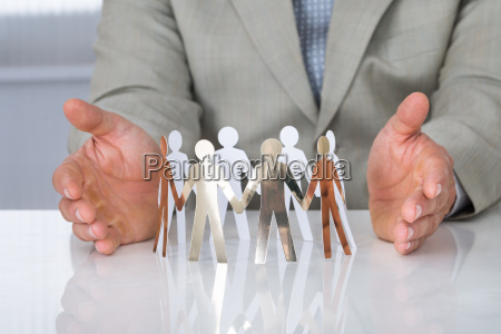businessman protecting paper team on desk