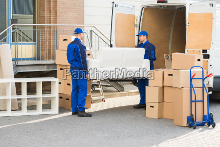 movers carrying sofa outside truck on
