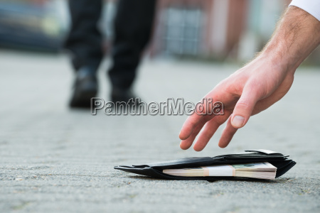businessman picking up fallen wallet with