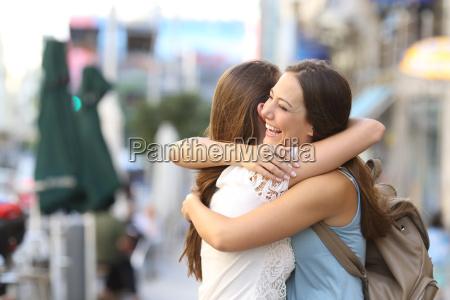 happy meeting of friends hugging