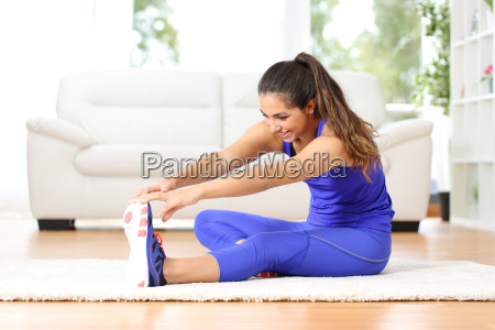 fitness woman stretching legs at home